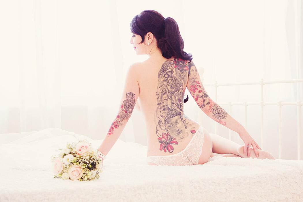 Brautdessous Foto - Braut mit Strauß auf dem Bett