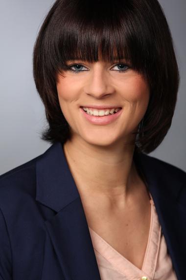 Das Bewerbungsbild zeigt eine Frau vor grauem Hintergrund.