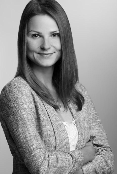 Das Bewerbungsbild zeigt eine Frau vor einem grauen Hintergrund in schwarz weiß.