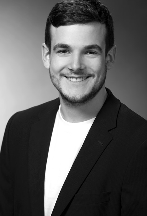 Das Bewerbungsbild zeigt einen Mann vor einem grauen Hintergrund in schwarz weiß.
