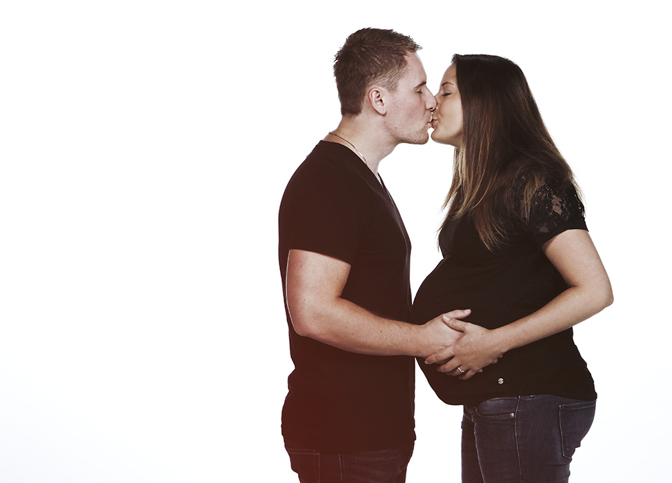Das Bild der Kategorie Babybauch zeigt ein Elternpaar, welches die Hände auf den Bauch der Mutter legt und sich küsst.